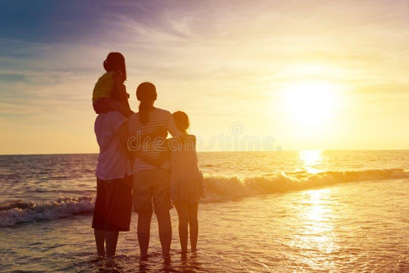 familie die op de zonsondergang op het strand letten royalty-vrije stock afbeelding