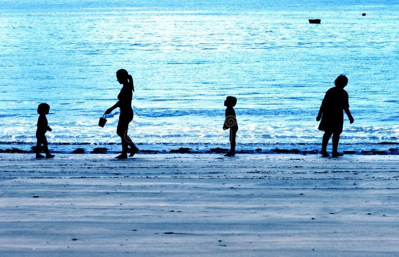 Familie die op een blauw avondstrand wordt gesilhouetteerd royalty-vrije stock afbeelding