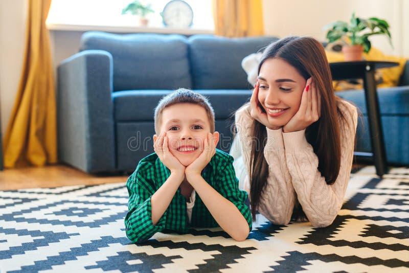 Familie die op een tapijt in hun woonkamer liggen royalty-vrije stock afbeeldingen