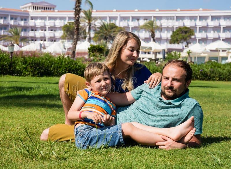 Familie die op gras op de achtergrond van hotel rusten stock fotografie