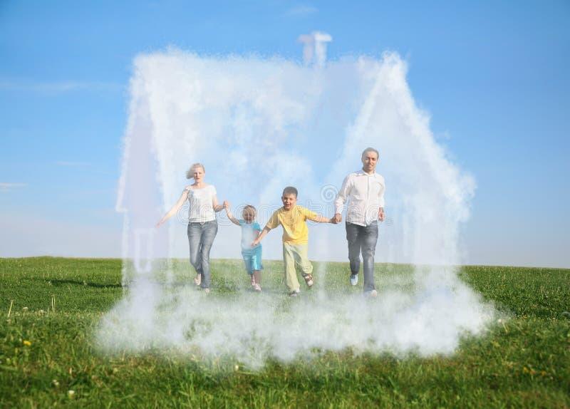 Familie die op gras en droomhuis loopt stock foto