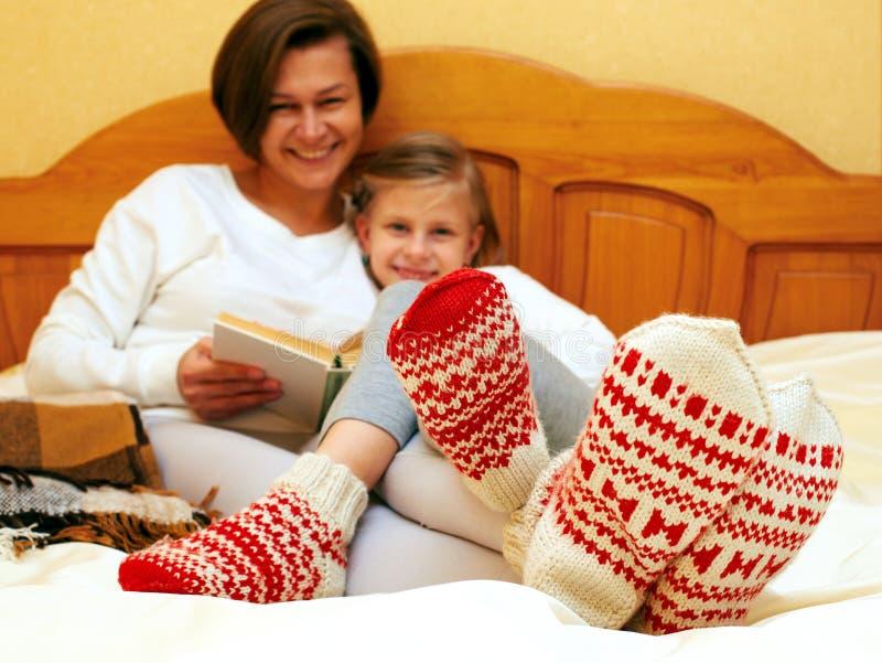 Familie die op het bed in gebreide sokken liggen royalty-vrije stock foto