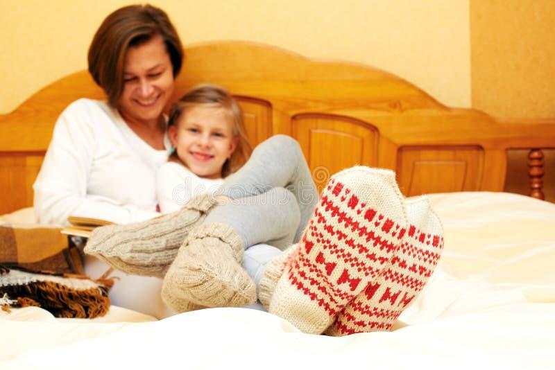 Familie die op het bed in gebreide sokken liggen royalty-vrije stock foto's