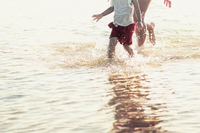 Familie die op het overzees in de zomer lopen stock afbeelding