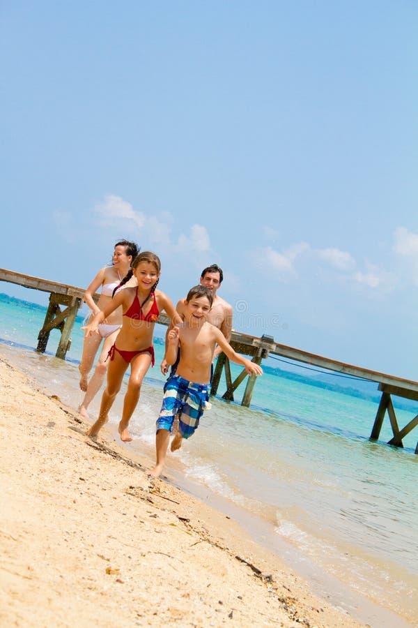 Familie die op het strand loopt royalty-vrije stock afbeeldingen