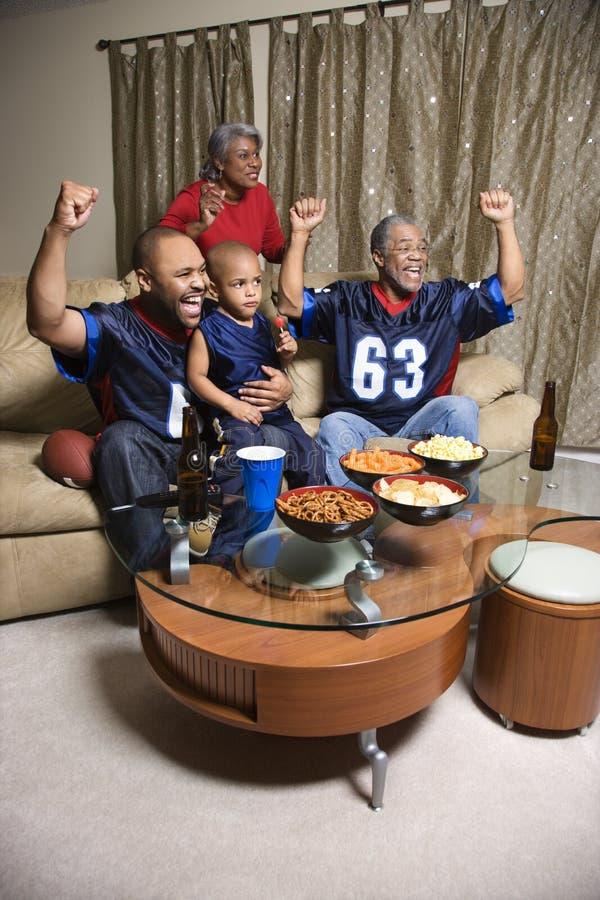 Familie die op het toejuichen van TV let