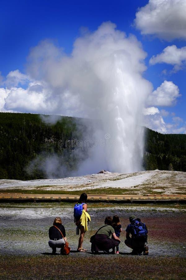 Familie die op Oude Gelovig in het Nationale Park van Yellowstone in Ame letten stock foto