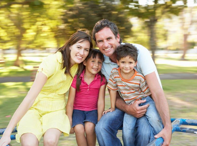 Familie die op Rotonde in Park berijdt stock foto's