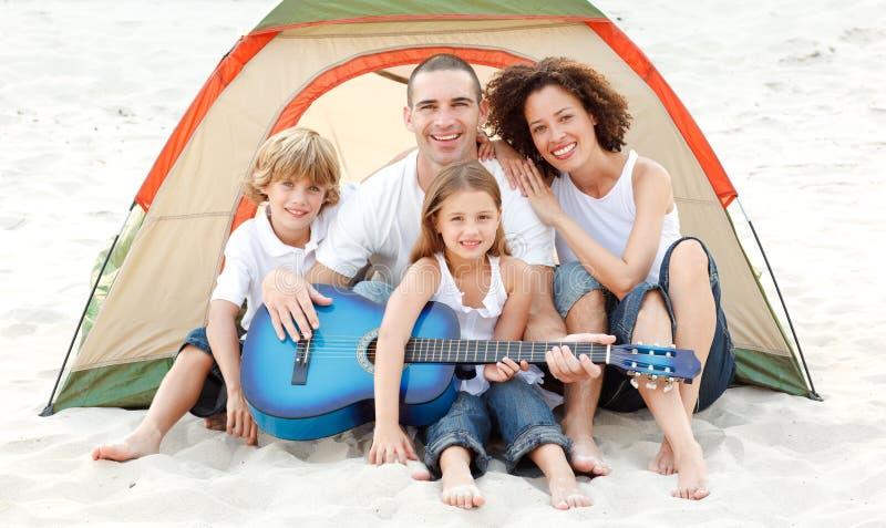Familie die op strand kampeert dat een gitaar speelt royalty-vrije stock foto's