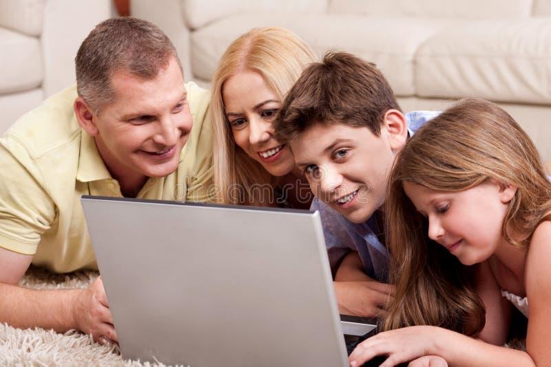 Familie die op tapijt in woonkamer met laptop ligt stock foto's