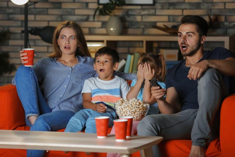 Familie die op TV op bank in avond letten stock afbeeldingen