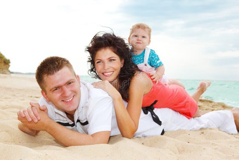 Familie die op zand ligt stock afbeeldingen