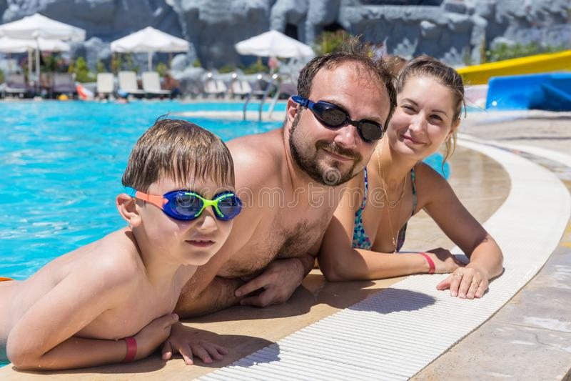 Familie die in openluchtpool zwemmen stock fotografie