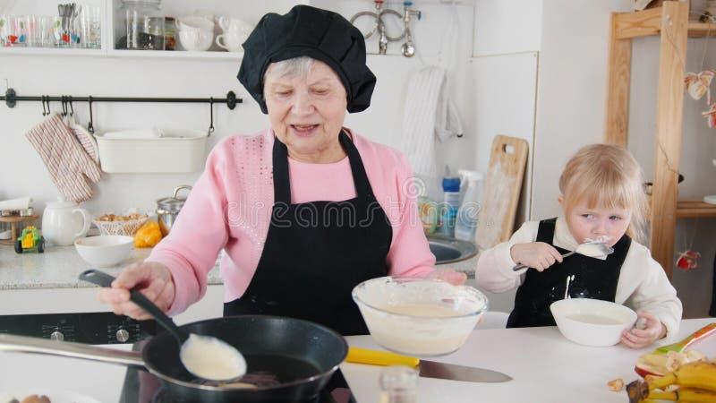Familie die pannekoeken maken Het oud vrouwen braden en een meisje die het deeg proeven stock foto's