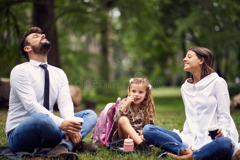 Familie die in park na school en het werk rusten stock foto