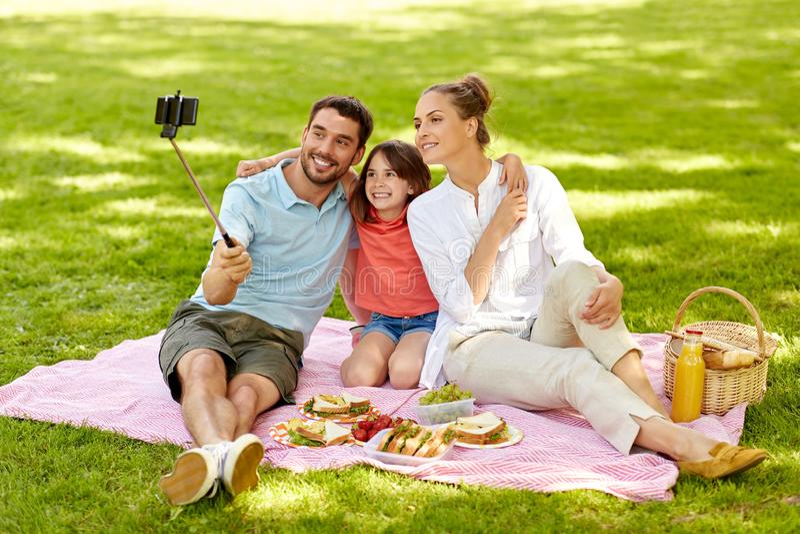 Familie die picknick hebben en selfie bij park nemen stock foto