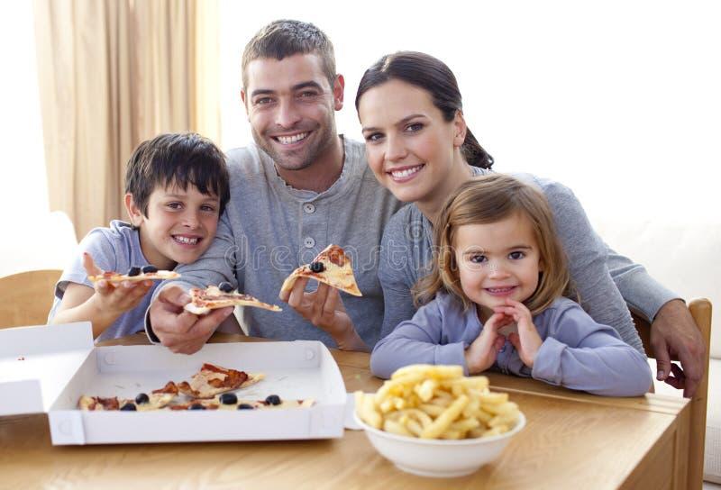 Familie die pizza en gebraden gerechten thuis eet royalty-vrije stock fotografie