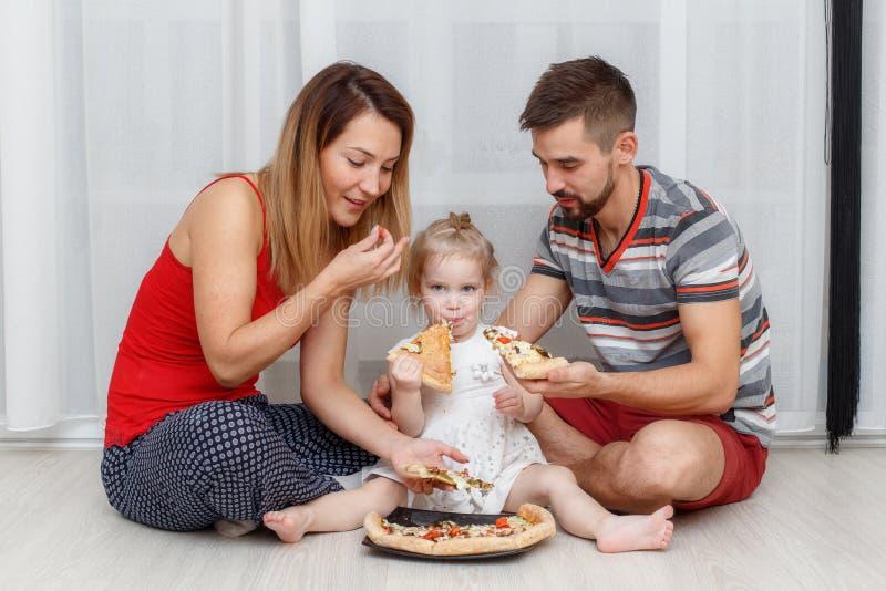 Familie, die Pizza isst Vater, Mutter und Tochter zu Hause lizenzfreie stockfotografie