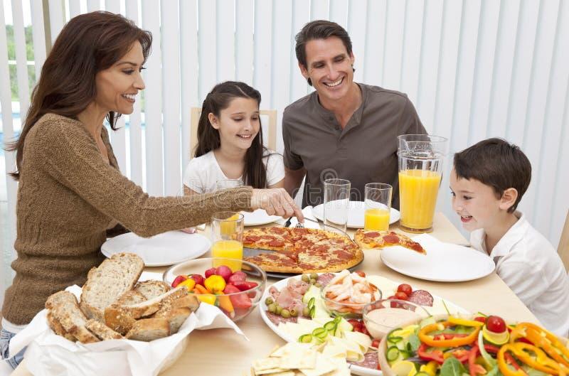 Familie, die Pizza u. Salat an Speisetische isst lizenzfreies stockbild