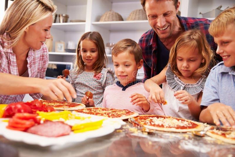 Familie die pizza voor diner maken royalty-vrije stock afbeeldingen
