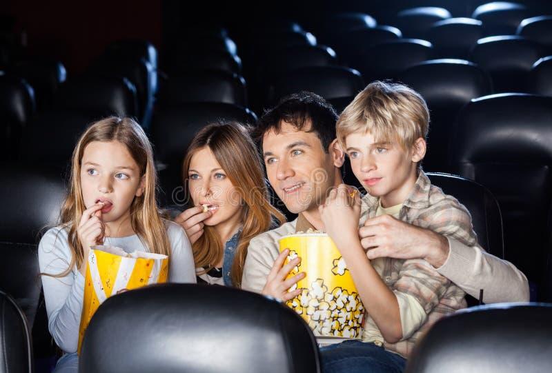 Familie, die Popcorn beim Film herein aufpassen isst lizenzfreies stockfoto