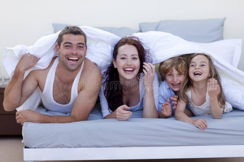 Familie die pret in bed heeft royalty-vrije stock foto