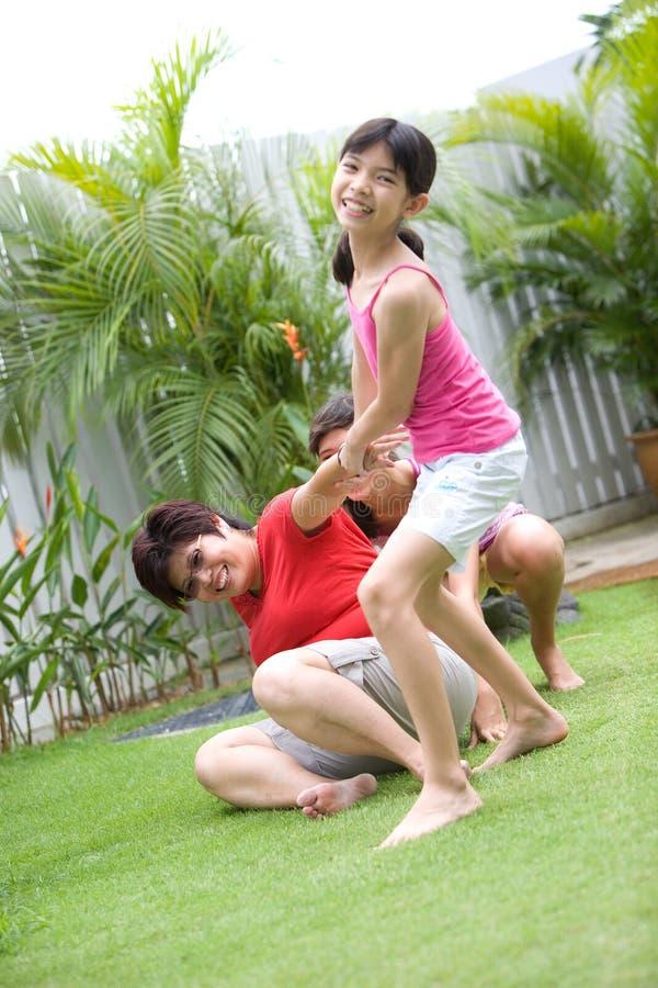 Familie die pret in de tuin heeft stock fotografie