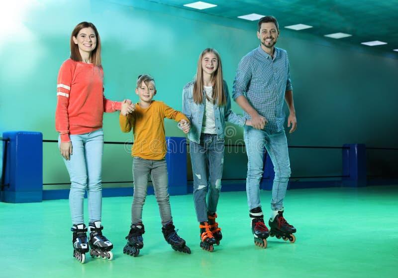 Familie die pret hebben bij rol het schaatsen piste stock afbeelding