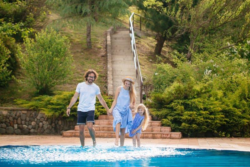 Familie die pret hebben hun pool dient het familie bespattende water met benen of zwembad in stock foto's