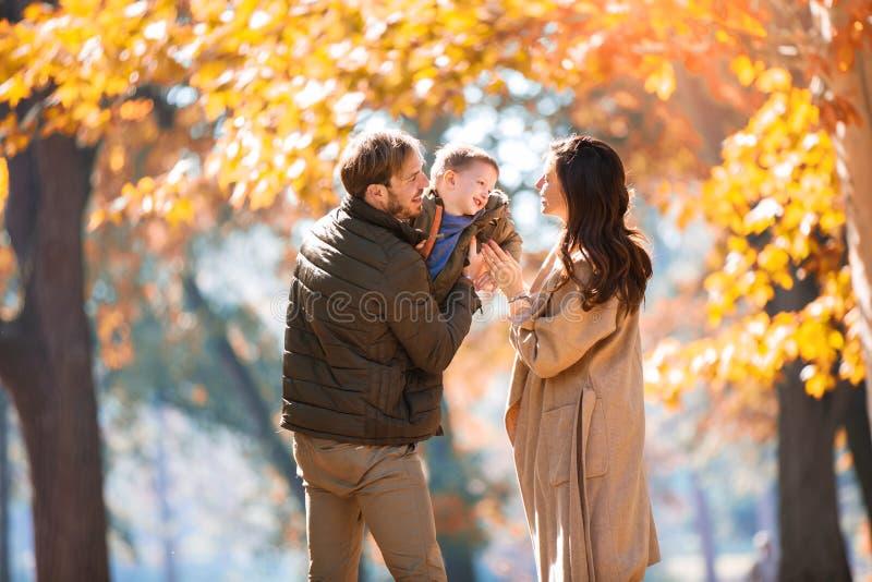 Familie die pret in het de herfstpark hebben met zijn zoon stock fotografie