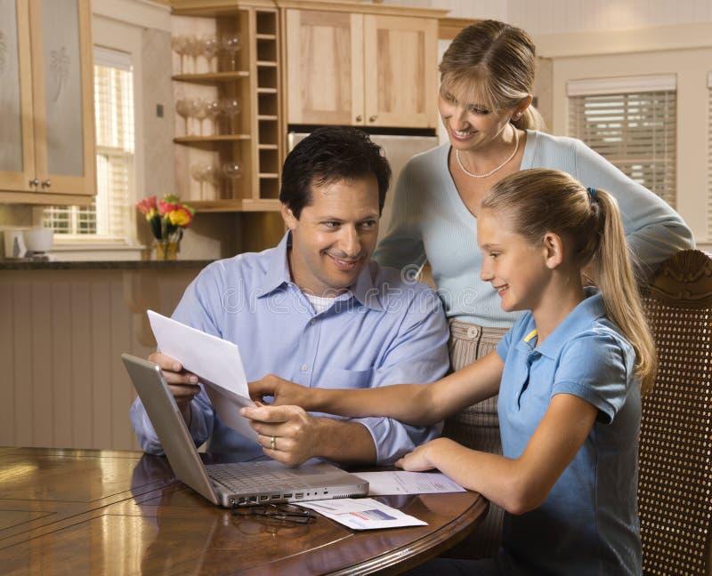 Familie die rekeningen op computer betaalt.