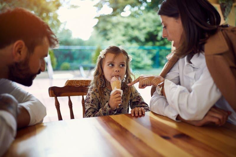 Familie die roomijs na school en het werk eten stock foto