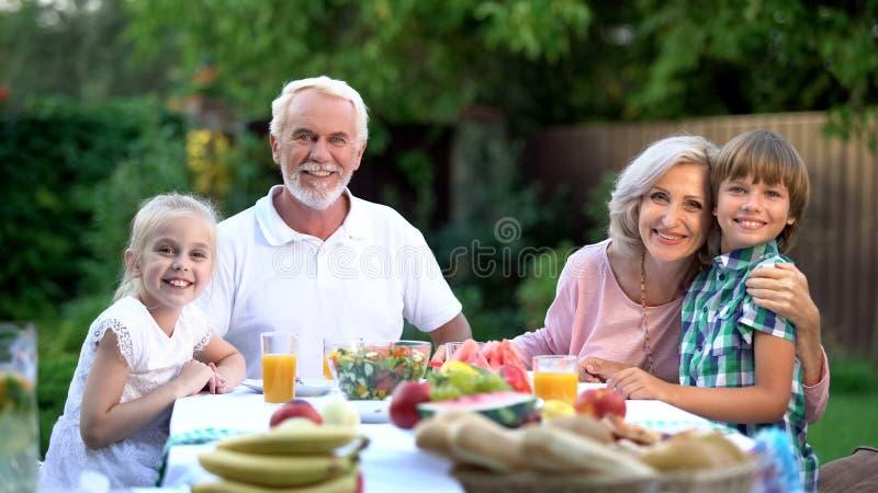 Familie die samen in openlucht en camera, zeker over toekomst bekijken dineren royalty-vrije stock fotografie