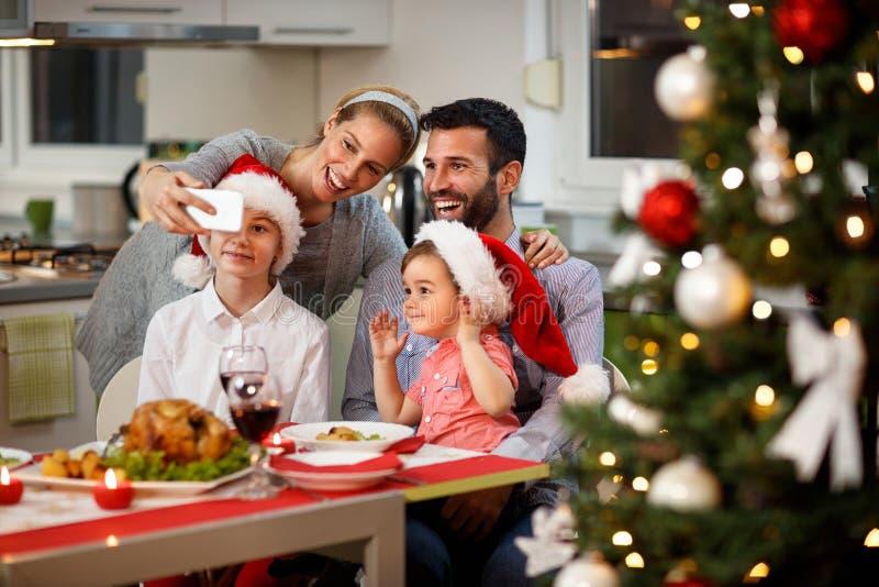 Familie die selfie bij verfraaide Kerstmislijst nemen stock afbeelding