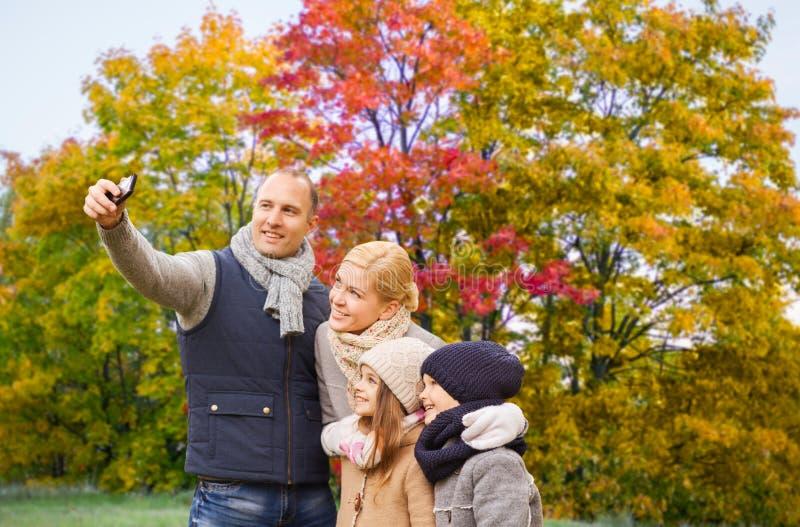 Familie, die selfie durch Smartphone im Herbstpark nimmt stockfotografie