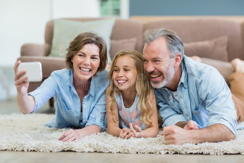 Familie die selfie uit mobiele telefoon nemen terwijl het liggen samen op tapijt in woonkamer stock fotografie