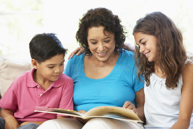 Familie, die sich zu Hause entspannt, ein Buch lesend stockbild