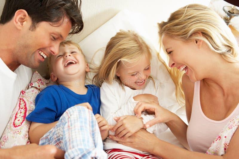 Familie, die sich zusammen im Bett entspannt lizenzfreies stockbild
