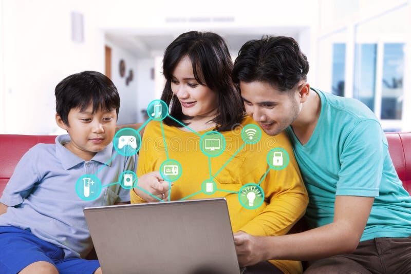 Familie die slim huissysteem op laptop met behulp van stock fotografie