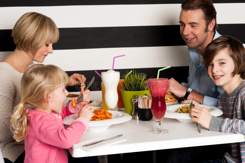 Familie, die Smoothies im Restaurant röstet lizenzfreie stockfotos