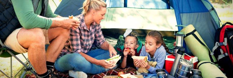 Familie die snacks buiten de tent hebben stock fotografie