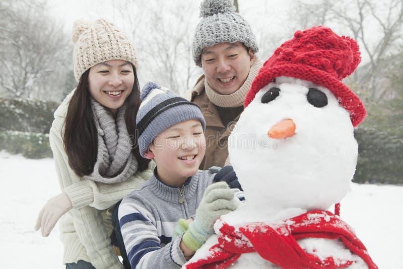 Familie die sneeuwman in een park in de winter maken royalty-vrije stock afbeelding