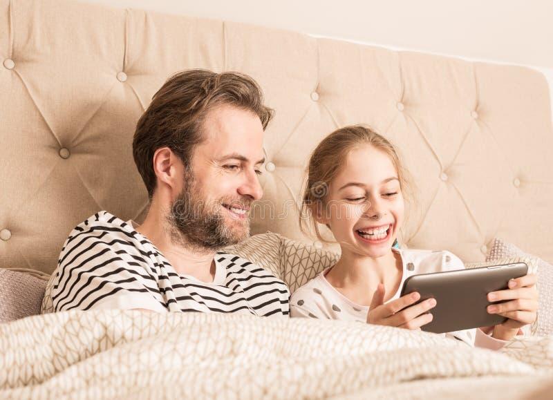 Familie, die Spaß bei der Anwendung der Tablette in einem Bett hat stockbild