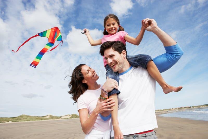 Familie, die Spaß-Fliegen-Drachen auf Strandurlaub hat lizenzfreie stockbilder