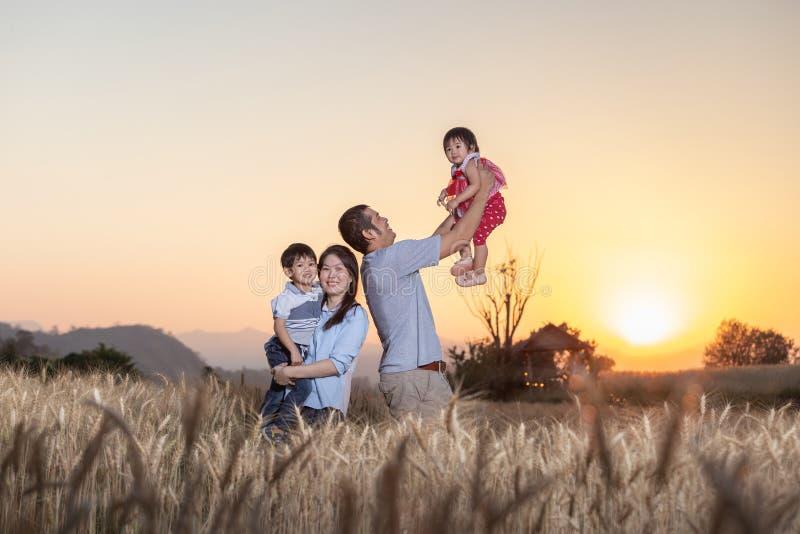 Familie, die Spaß hat und auf einem Gerstengebiet im Sommer zur Sonnenuntergangzeit spielt stockfotos