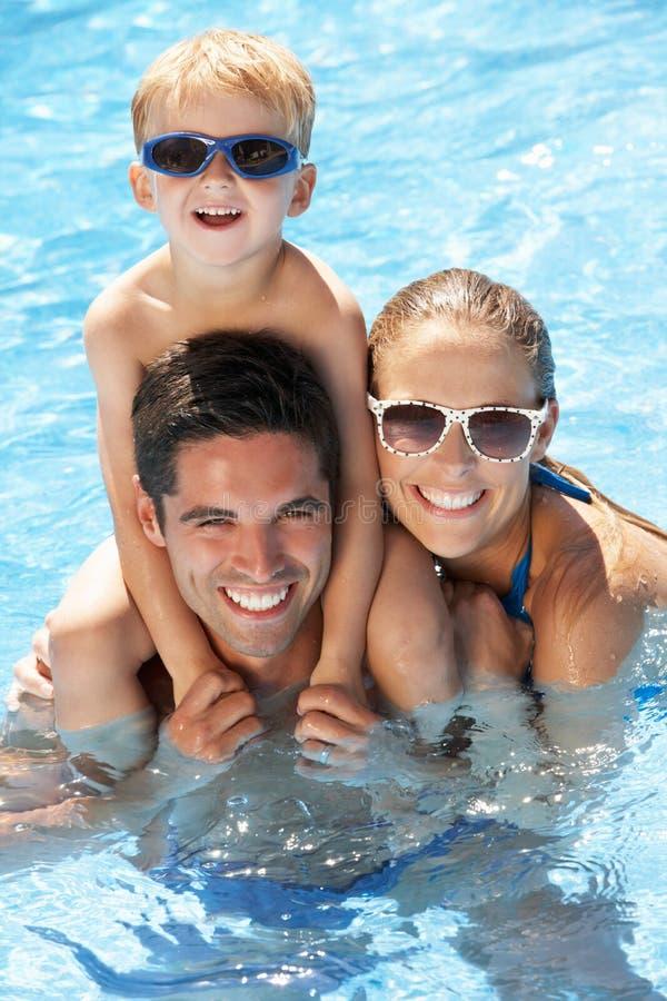Familie, die Spaß im Swimmingpool hat stockfotos