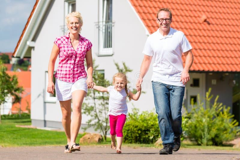 Familie, die Spaziergang vor Haus macht lizenzfreie stockfotos