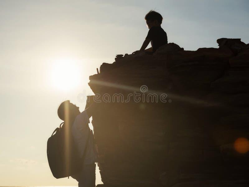 Familie, die Tätigkeit zur Hügelspitze bei Sonnenuntergang wandert stockfoto