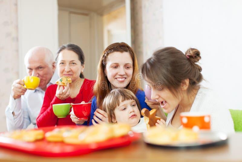 Familie die thee met cakes hebben royalty-vrije stock afbeelding