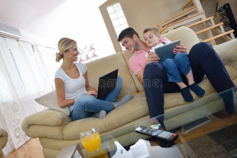 Familie die thuis tabletcomputer met behulp van stock foto
